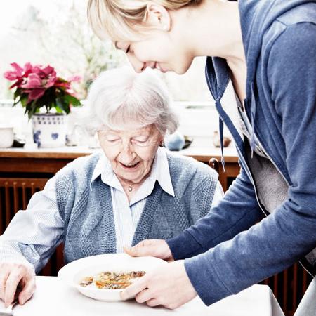 Altenpflegehelferin kümmert sich um die Verpflegung